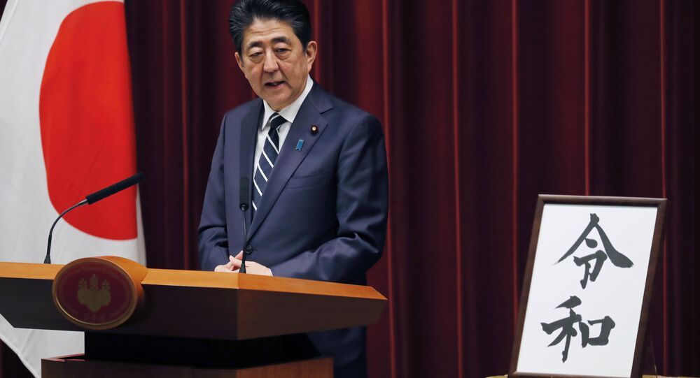 Japanese Prime Minister Shinzo Abe stands beside the Japanese characters of kanji which make up Reiwa, the new imperial era