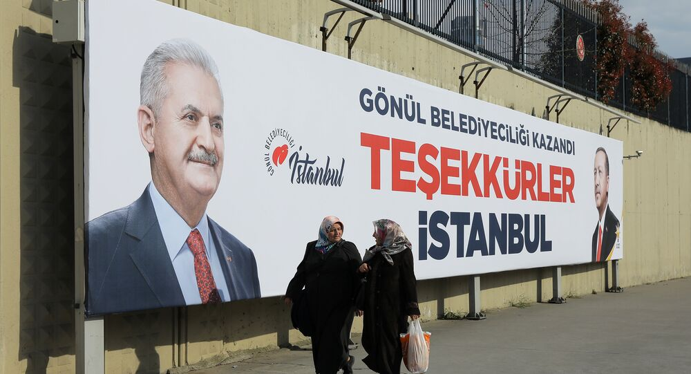 People walk past by AK Party billboards with pictures of Turkish President Tayyip Erdogan and mayoral candidate Binali Yildirim in Istanbul, Turkey, April 1, 2019.