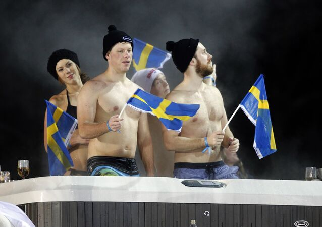 Spectators wave Swedish flags as they enjoy a sauna while following the alpine ski, men's World Cup city event in Stockholm, Tuesday, Jan. 30, 2018