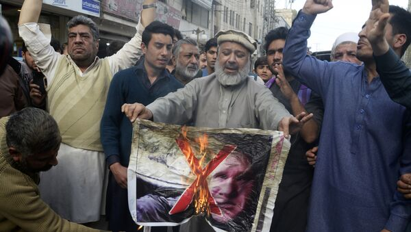 Pakistan traders burn a poster with the image of Brenton Tarrant, the man charged in relation against the March 15 attack on two mosques in Christchurch, during a protest in Peshawar on March 16, 2019 - Sputnik International