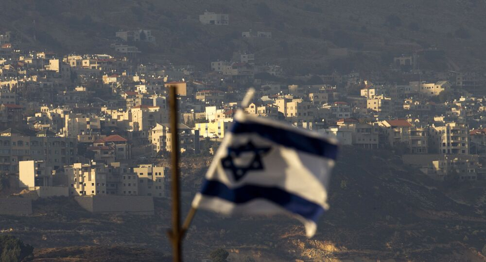 An Israeli flag flies in front of the village of Majdal Shams in the Israeli-controlled Golan Heights on 11 October 2018. Syria slammed President Donald Trump's abrupt declaration that Washington will recognise Israel's sovereignty over the Israeli-occupied Golan Heights, saying the statement was irresponsible and a threat to international peace.