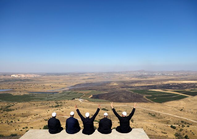 Israeli Druzes sit together watching the Syrian side of the Israel-Syria border on the Israeli-occupied Golan Heights, Israel July 7, 2018