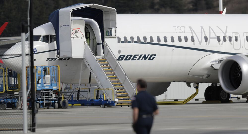 A worker walks next to a Boeing 737 MAX 8 airplane parked at Boeing Field, Thursday, March 14, 2019, in Seattle