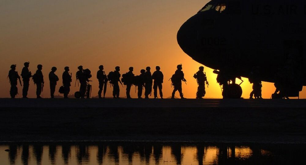 The sun sets behind a C-17 Globemasterat Joint Base Balad, Iraq, as Soldiers begin boarding