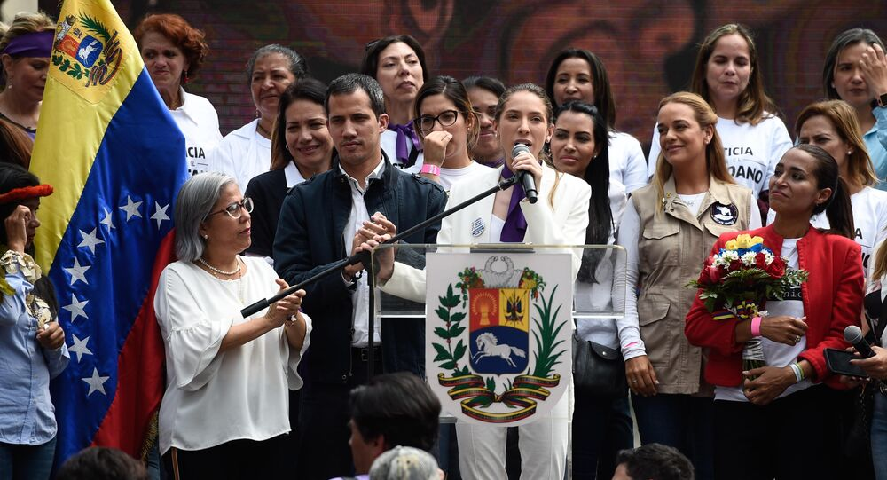 Fabiana Rosales (C), wife of Venezuelan opposition leader and self-declared acting president Juan Guaido (L), speaks next to her husband during a rally on the International Women's Day in Caracas on March 8, 2019.