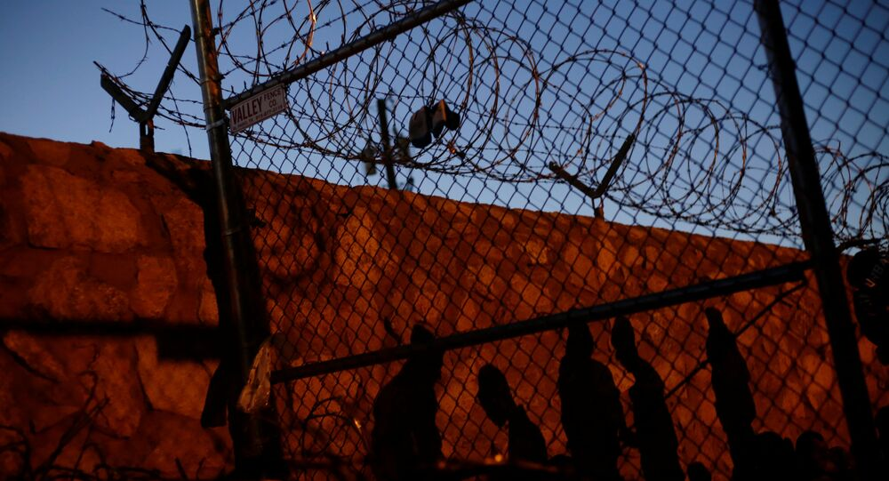 Central American migrants cast their shadows against a wall while inside an enclosure where they are being held after turning themselves in to request asylum, in El Paso