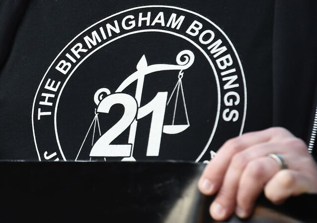 A man wears a t-shirt with a logo representing justice for the 21 victims of the Birmingham pub bombings in 1974