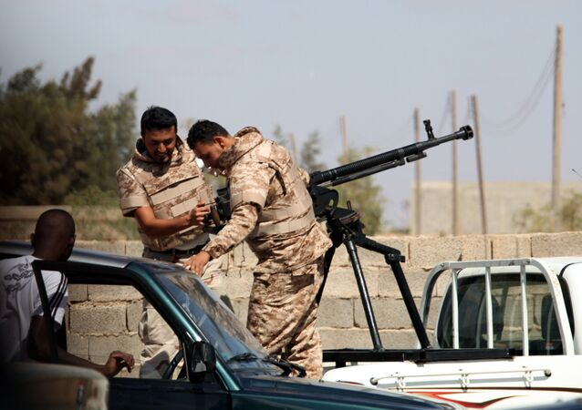 Soldiers from the Libyan National Army get ready to enter Rafallah al-sahati Islamic Militia Brigades compound, one of the compound buildings can be seen behind the wall, in Benghazi, Libya, Saturday, Sept. 22, 2012.
