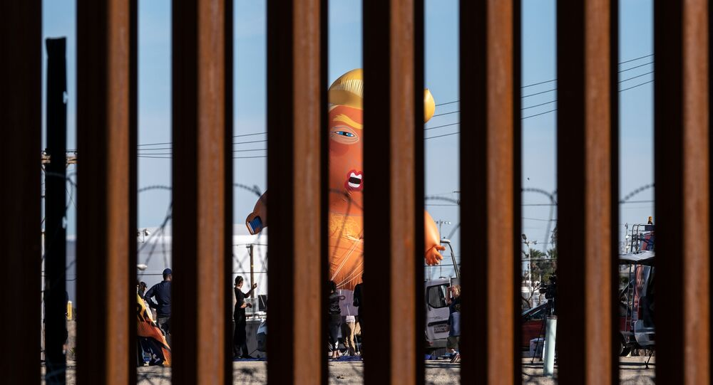 A satirical balloon of a baby US President Donald Trump is seen through the US-Mexico border fence during a demonstration against him prior to his visit to Calexico, California, as seen from Mexicali, Baja California state, Mexico, on April 5, 2019.