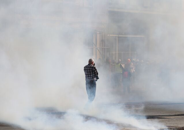 A man stands in tear-gas smoke during a Yellow Vests (Gilets Jaunes) protest in Rouen on April 6, 2019 as demonstrations are planned by the Yellow Vest movement for the 21st consecutive Saturday