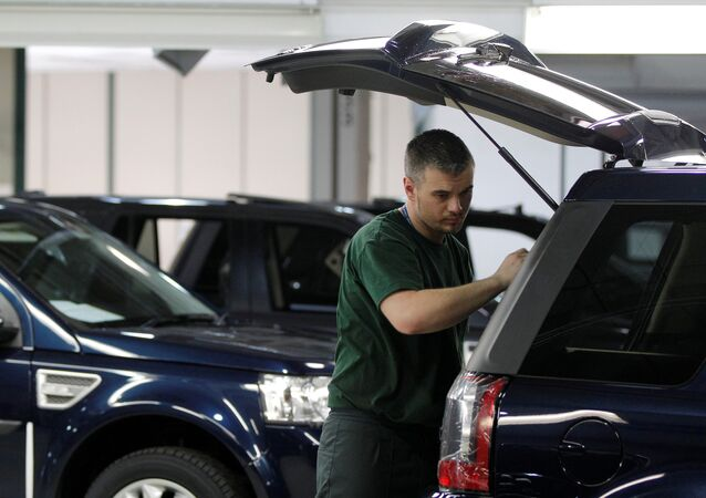 Workers examine Land Rover Freelander vehicles as they come off the production line at Jaguar Land Rover's Halewood assembly plant in Liverpool