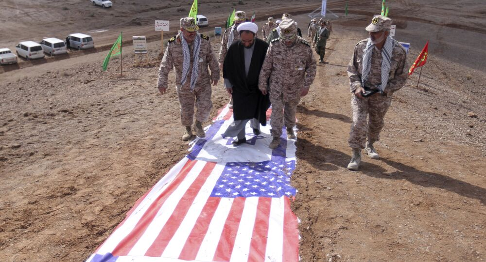 Members of Iran's Revolutionary Guard and a clergyman walk on the representations of the U.S. and Israeli flags
