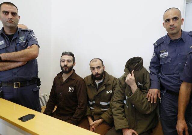 French national Romain Franck (R), 24, a worker at the French consulate, and Palestinian Moufak al-Ajluni (L) and Mohamed Katout (C) appear in court the southern Israeli city of Beer Sheva on March 19, 2018, to face charges of smuggling guns from Gaza
