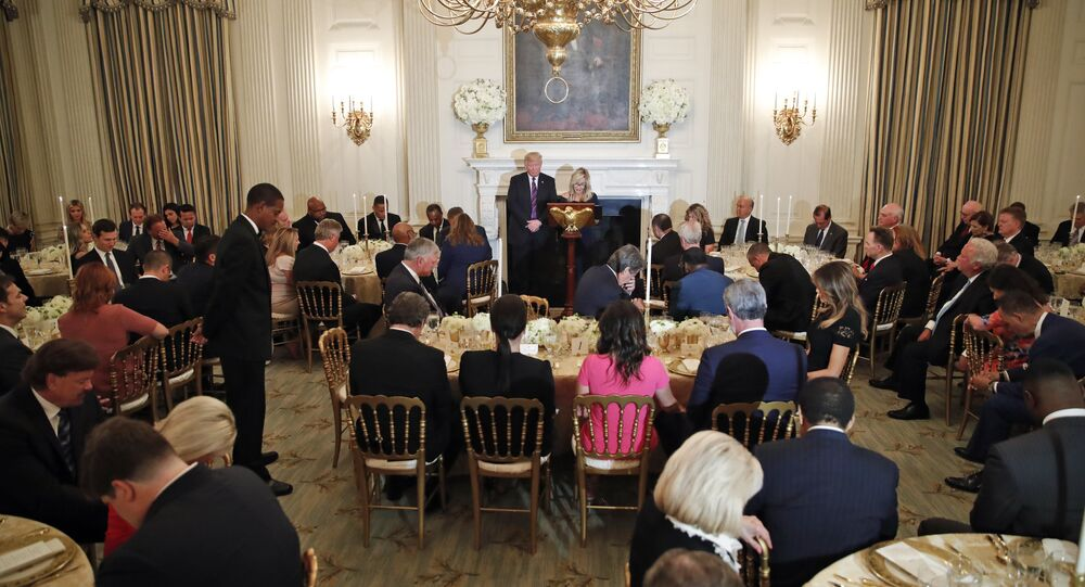 President Donald Trump bows his head as pastor Paula White leads the room in prayer during a dinner for evangelical leaders in the State Dining Room of the White House on 27 August 2018