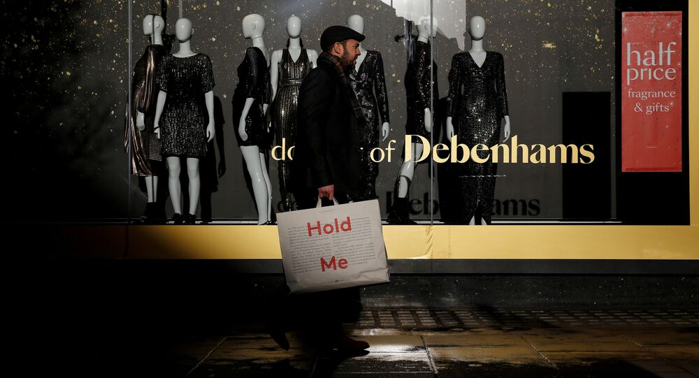 Shoppers walk past a window display at the Debenhams department store on Oxford Street in London