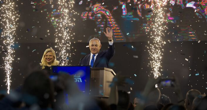 Israel's Prime Minister Benjamin Netanyahu accompanied by his wife Sara waves to his supporters after polls for Israel's general elections closed in Tel Aviv, Israel, Wednesday, April 10, 2019