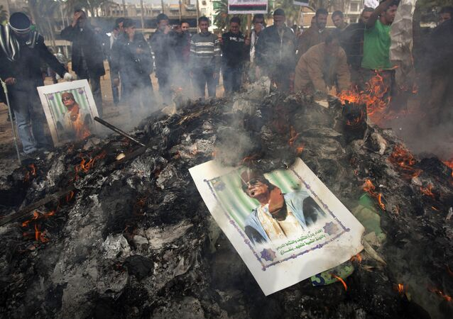 Libyan protesters burn a poster of Libyan leader Moammar Gadhafi as it is burned during a demonstration against him in Benghazi, eastern Libya, Wednesday, March 2 , 2011