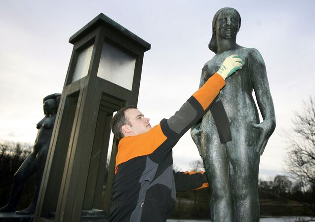 Municipal worker Matthew Wills removes black strips of paper from a statue by Norwegian sculptor Gustav Vigeland in Vigeland Park in Oslo 15 March 2007