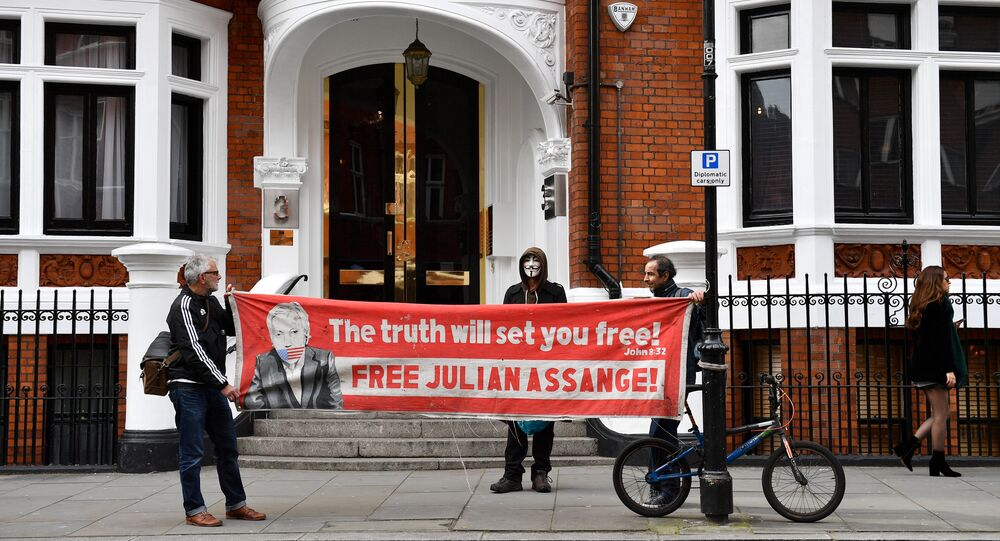 Suporters of WikiLeaks founder Julian Assange hold a banner as they gather outside the Ecuadorian Embassy in London on April 5, 2019, following rumours that Assange was about to be expelled