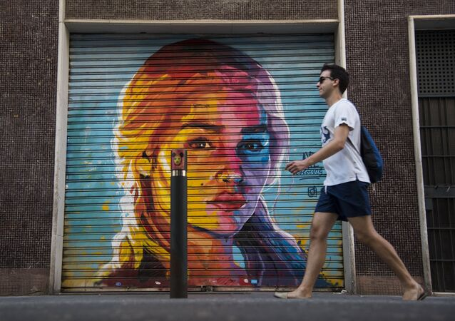 A man walks in front of a graffiti by street artist Axe Colours portraying British actress Emilia Clarke known for playing Daenerys Targaryen in The Game of Thrones TV series in Barcelona on July 30, 2017