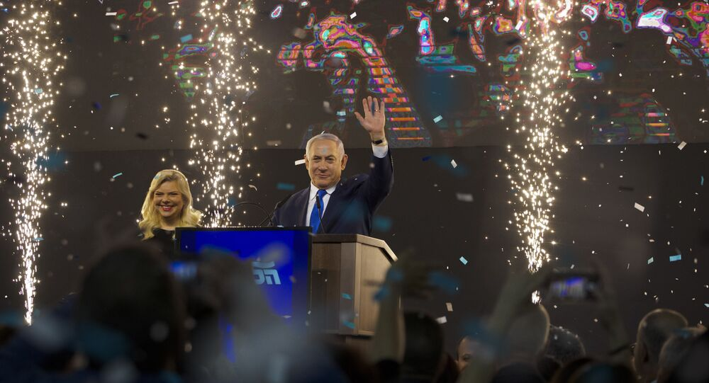 Israel's Prime Minister Benjamin Netanyahu accompanied by his wife Sara waves to his supporters after polls for Israel's general elections closed in Tel Aviv, Israel, Wednesday, April 10, 2019.