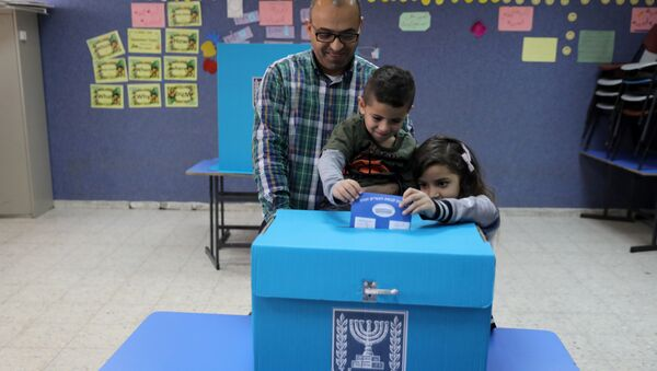 An Israeli-Arab father casts a ballot together with his children, as Israelis vote in a parliamentary election, at a polling station in Umm al-Fahm, Israel - Sputnik International