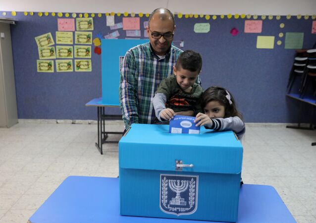 An Israeli-Arab father casts a ballot together with his children, as Israelis vote in a parliamentary election, at a polling station in Umm al-Fahm, Israel