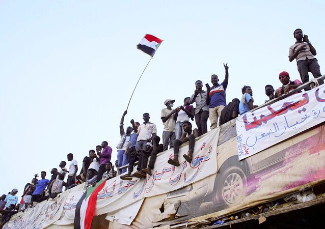 Demonstrators wave their national flag as they attend a protest rally demanding Sudanese President Omar Al-Bashir to step down outside Defence Ministry in Khartoum, Sudan April 10, 2019.