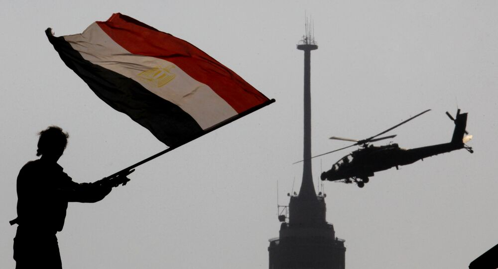 An opponent of Egypt's ousted president Mohammed Morsi waves a national flag as a military helicopter flies over Tahrir Square in Cairo, Egypt, Friday, July 5, 2013