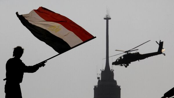 An opponent of Egypt's ousted president Mohammed Morsi waves a national flag as a military helicopter flies over Tahrir Square in Cairo, Egypt, Friday, July 5, 2013 - Sputnik International