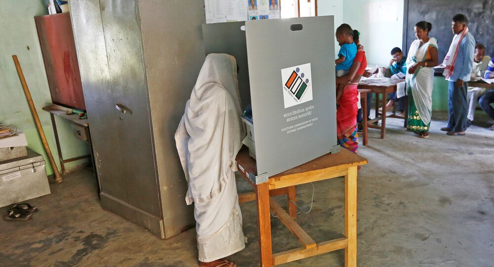 A woman casts her vote as others wait for their turn at a polling station during the first phase of general election in Majuli, a large river island in the Brahmaputra river, in the northeastern Indian state of Assam, India April 11, 2019
