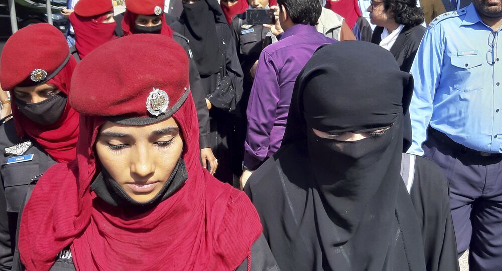 Pakistani girls from the Hindu community wearing black veils, arrive at a court in Islamabad, Pakistan, Tuesday, March 26, 2019. A Pakistani court placed two teenage sisters from the minority Hindu community in a government shelter on Tuesday as authorities launched an investigation into whether the girls were abducted and forced to convert and marry two Muslim men