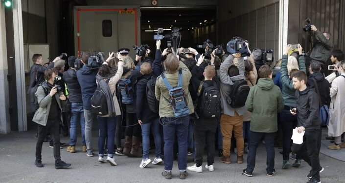 Media waiting for the arrival of WikiLeaks founder Julian Assange swarm around a car that arrives at Westminster magistrates court in London, Thursday, April 11, 2019