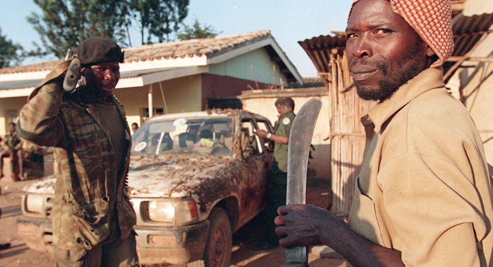 An armed Rwandan soldier and a member of the Interahamwe carrying a machete are seen in Gitarama during the genocide