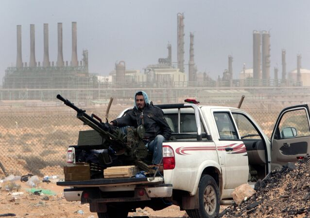 An anti-government rebel sits with an anti-aircraft weapon in front an oil refinery in Ras Lanouf, eastern Libya.