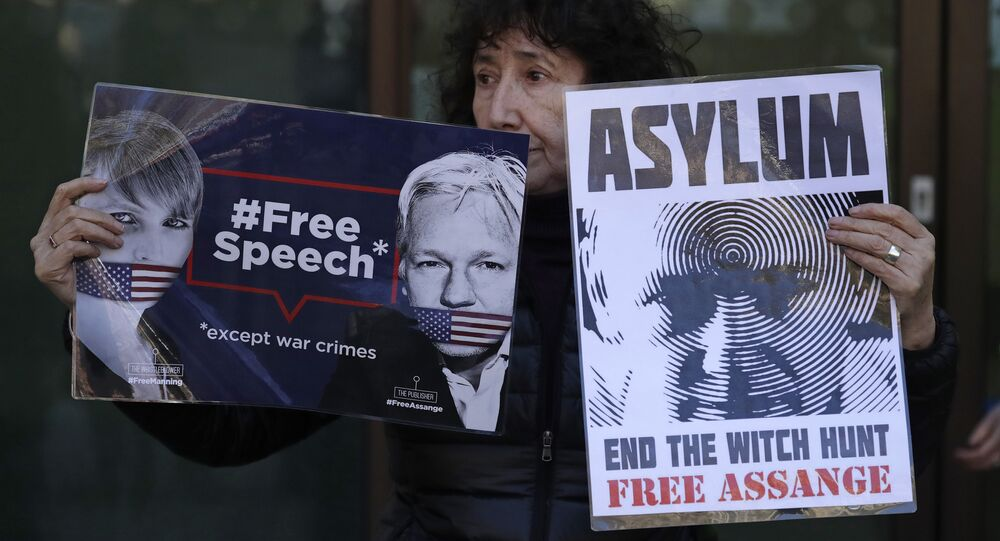 A protester demonstrating in support of WikiLeaks founder Julian Assange holds placards outside Westminster magistrates court where he was appearing in London, Thursday, April 11, 2019.