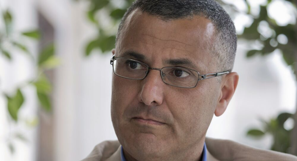Omar Barghouti listens during an interview with the Associated Press in the West Bank city of Ramallah, Tuesday, May 10, 2016. Barghouti, a Qatari-born Palestinian who is married to an Israeli woman and leader of the international boycott movement against Israel, on Tuesday accused Israeli authorities of imposing a travel ban on him as retribution for his political activities.