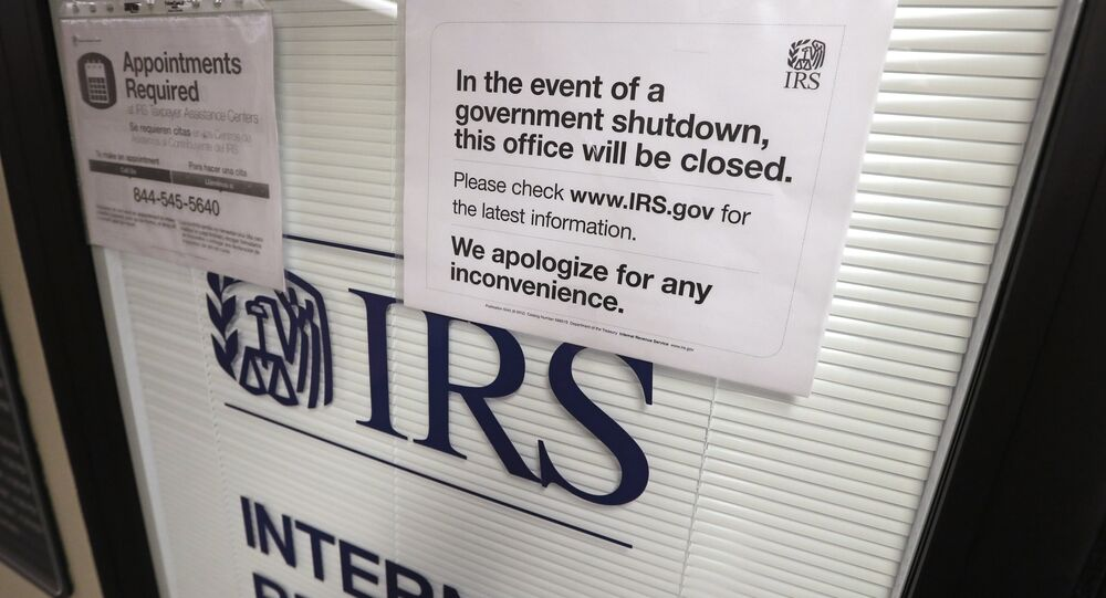 Doors at the Internal Revenue Service (IRS) in the Henry M. Jackson Federal Building are locked and covered with blinds as a sign posted advises that the office will be closed during the partial government shutdown
