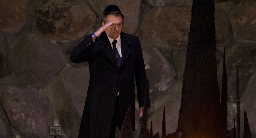 Brazil's President Jair Bolsonaro salutes during a ceremony commemorating the six million Jews killed by the Nazis during the Holocaust, in the Hall of Remembrance at Yad Vashem World Holocaust Remembrance Center Jerusalem, Tuesday, April 2, 2019.