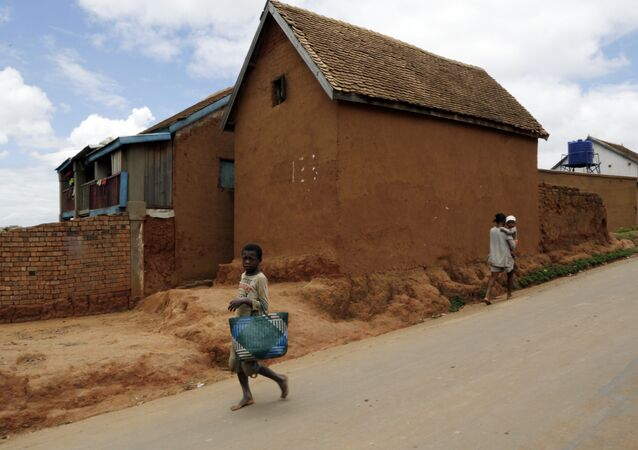 A young girl runs past a house in Antananarivo, Madagascar