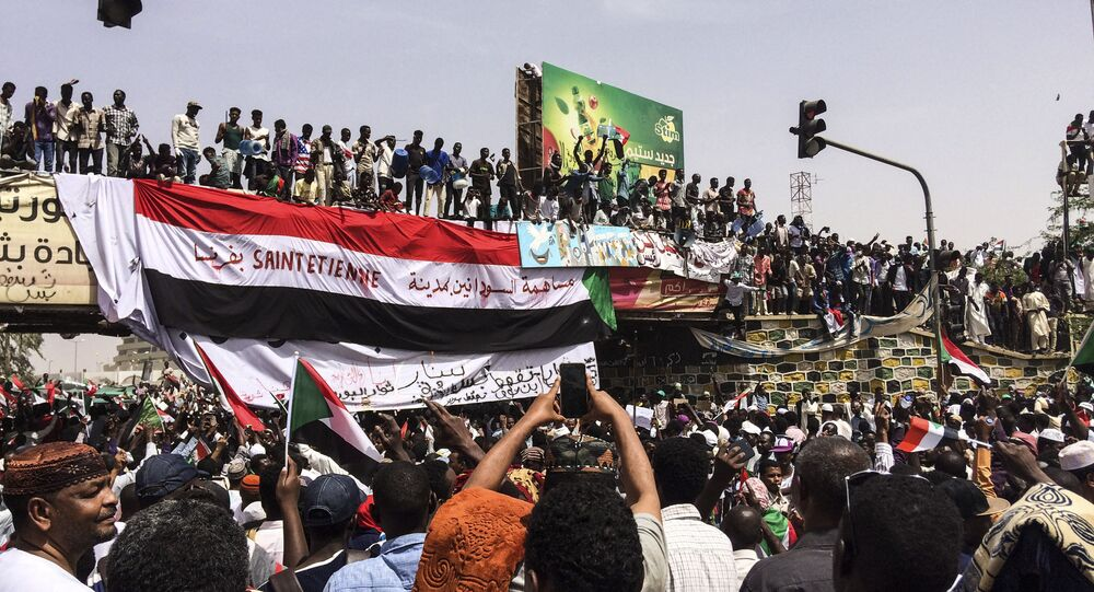 Demonstrators gather in Sudan's capital of Khartoum, Friday, April 12, 2019. The Sudanese protest movement has rejected the military's declaration that it has no ambitions to hold the reins of power for long after ousting the president of 30 years, Omar al-Bashir. The writing on the Sudanese flag says 'With the participation of the Sudanese in Saint Etienne, France.'