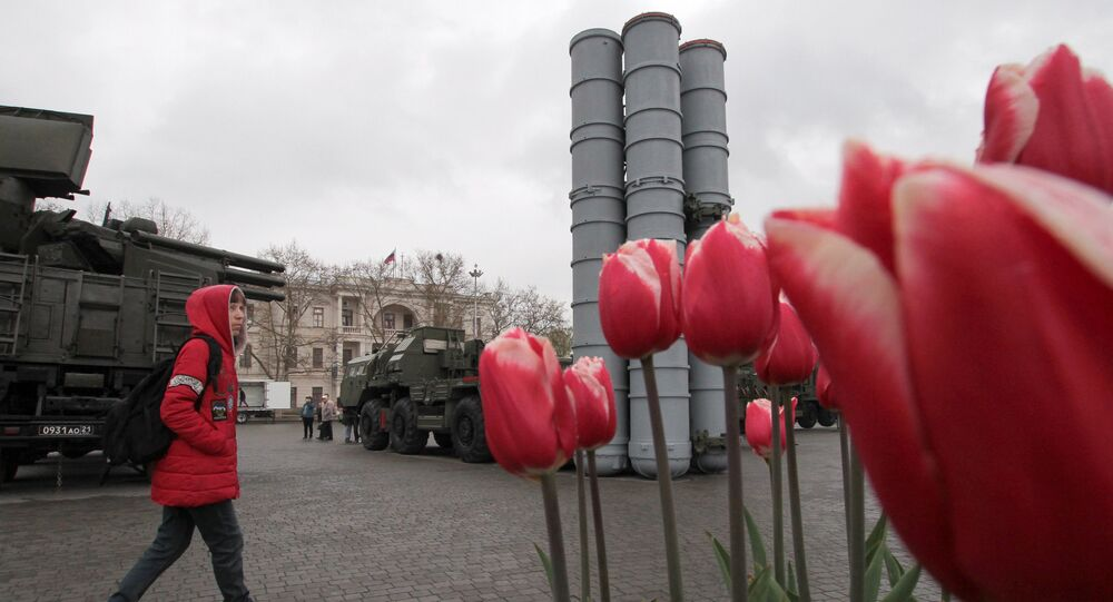 A visitor approaches a surface-to-air missile system S-400 Triumph during an exhibition displaying Russian military equipment, vehicles and weapons, with tulips seen in the foreground, in the Black Sea port of Sevastopol, Crimea April 12, 2019