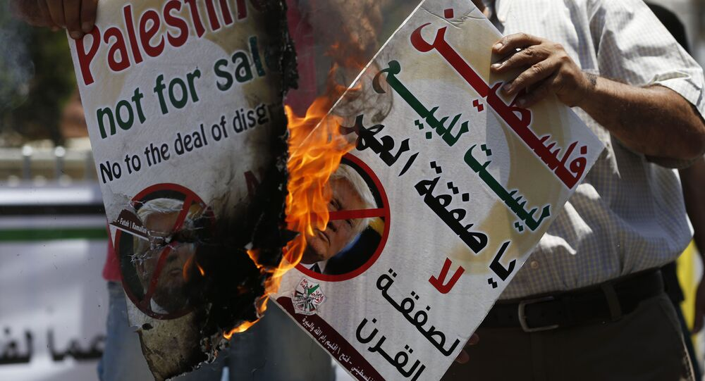 Palestinians burn portraits of US President Donald Trump during a demonstration in the West Bank city of Ramallah against US policy supporting Israel on July 2, 2018