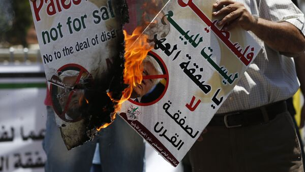 Palestinians burn portraits of US President Donald Trump during a demonstration in the West Bank city of Ramallah against US policy supporting Israel on July 2, 2018 - Sputnik International