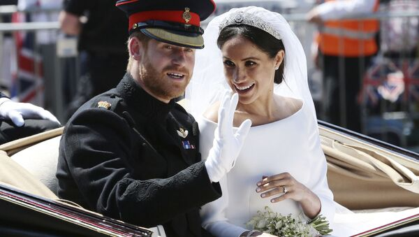 Britain's Prince Harry and Meghan Markle ride in an open-topped carriage after their wedding ceremony at St. George's Chapel in Windsor Castle in Windsor, near London, England, Saturday, May 19, 2018 - Sputnik International