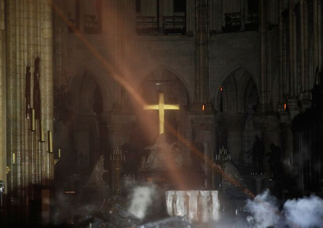 Smoke rises around the alter in front of the cross inside the Notre Dame Cathedral as a fire continues to burn in Paris, France, April 16, 2019.