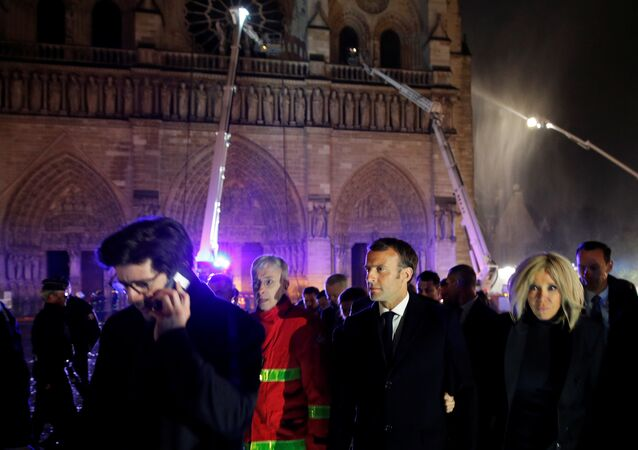 French President Emmanuel Macron and his wife Brigitte walk outside the Notre Dame Cathedral where a fire continues to burn in Paris on April 16, 2019.