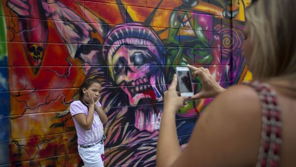 In this March 19, 2015 file photo, a girl poses for a picture in front of a mural depicting the statue of liberty as death, at Bolivar square in Caracas, Venezuela - Sputnik International