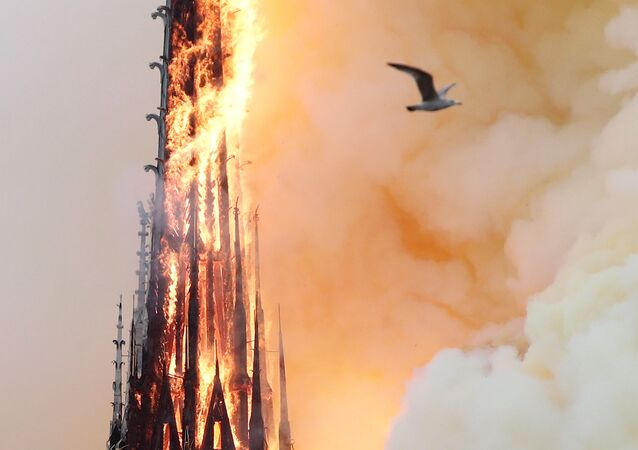 Smoke billows as fire engulfs the spire of Notre Dame Cathedral in Paris, France April 15, 2019