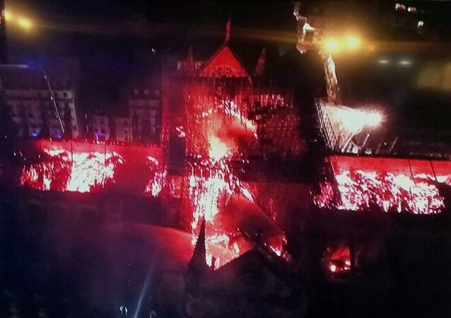 An image taken from a television screen shows an aerial view of the Notre Dame Cathedral engulfed in flames on 15 April, 2019, in the French capital Paris